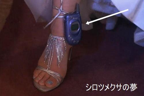 靴のストラップにひっかけたガラケー。